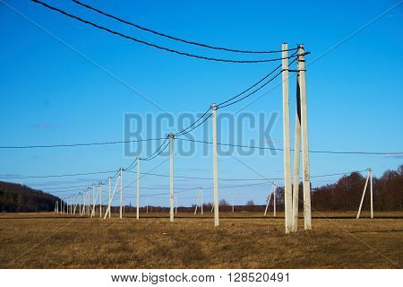 Electric poles with wires on the meadow in the countryside with trees in the background