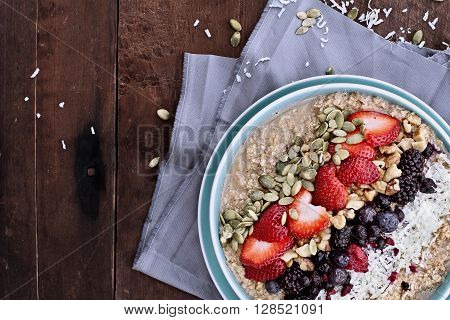 Hot breakfast of healthy oatmeal with shredded coconut blackberries blueberries walnuts heart shaped strawberries and pumpkin seeds over a rustic background. Image shot from overhead.