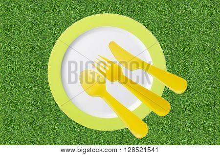 empty plate with yellow spoons and forks on green grass