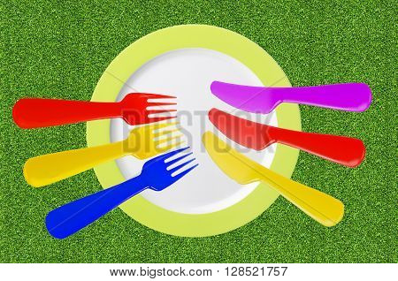 empty plate with color knives and forks on green grass