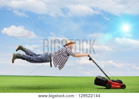 Mature man being pulled by a powerful lawnmower outdoors on a beautiful sunny day
