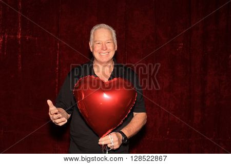 A happy man smiles while posing for his photos in a Photo Booth. Photo Booths are very popular for all parties and especially weddings. Everyone loves a good photo booth.