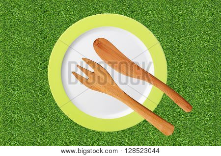 empty plate and wooden fork and knife on green grass