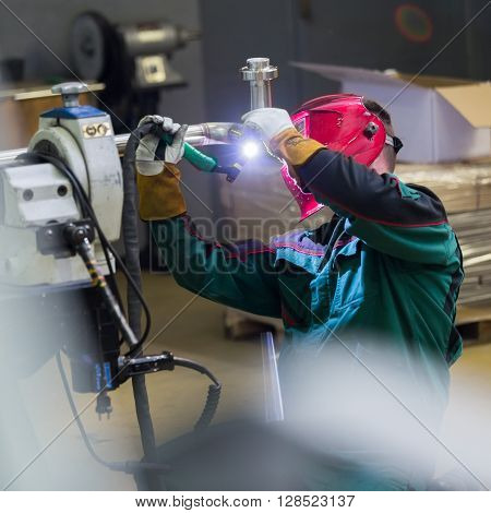 Industrial worker with protective mask welding inox elements in steel structures manufacture workshop. Square composition.