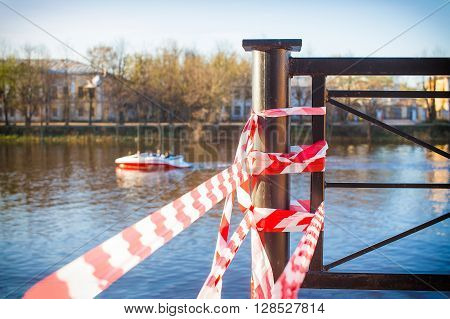 safety tape on the embankment of the river. crossing barrier tape insulates a dangerous place on the river bank