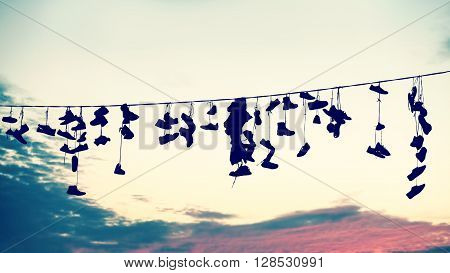 Retro Stylized Silhouettes Of Shoes Hanging On Cable.