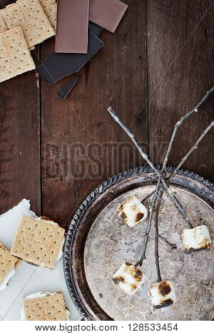 Smores and ingredients over a rustic wooden background.