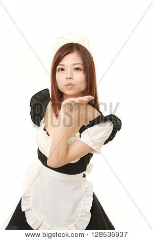 young Japanese woman wearing french maid costume blowing a kiss