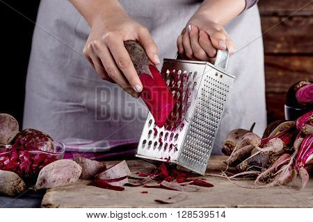 Cook in gray apron is grating a beetroot with vegetable rasper