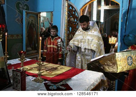 VOYUTYN UKRAINE - JANUARY 08: Orthodox priest and little sexton during Christmas service in Voyutyn on January 08 2009.