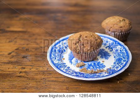 Fresh homemade muffins on a plate on a wooden table ** Note: Shallow depth of field