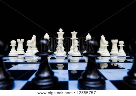White chess pieces in set up position viewed from back line of black. Worm view as if in the eye of a black piece looking at the threatening white army.
