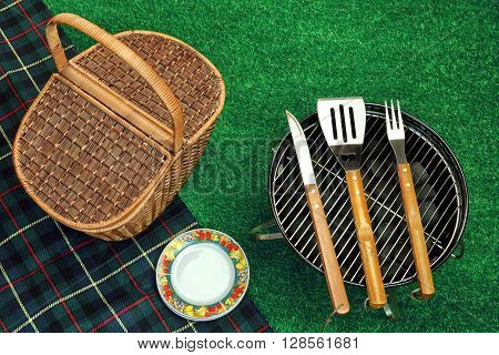 Portable Barbecue Grill On Lawn, Tools, Picnic Basket And Blanket