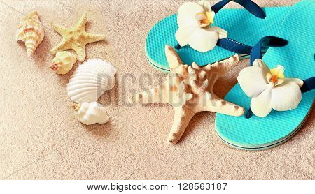Flip Flops in the sand with starfish and orchid flowers. Summertime on beach concept. Summer beach.