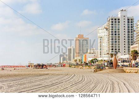 Mediterranean Sea beach with hotels along embankment against blue sky background. Tel Aviv, Israel.