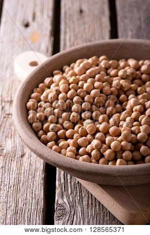 Clay Bowl With Dried Chickpeas On Wooden Board