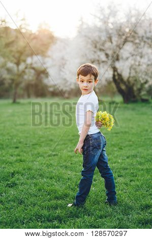 boy standing in park and holding behind bouquet of wildflowers
