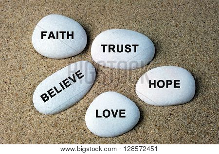 Faith trust believe hope and love text on a stones with sand background poster
