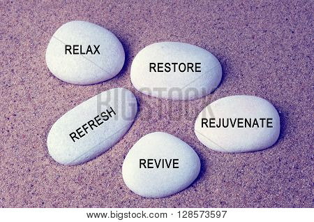 Wellness spa and beauty concept - Relax restore refresh rejuvenate and revive text on zen stones retro style background