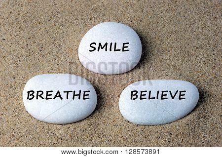 Smile breathe and believe text on zen stone.