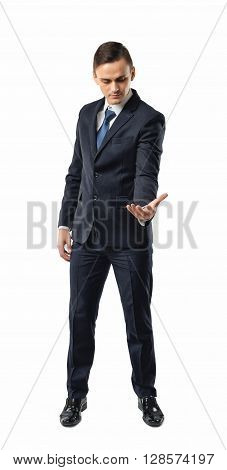 Businessman holding something in his palm and looking to it. Palm up. Successful lifestyle. Business staff. Office clothes. Dress code. Presentable appearance. Self-confidence.