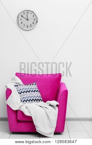 Pink armchair with blanket and pillow on light wall background