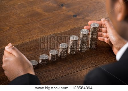 Close-up Of Businessperson Hand Protecting Stacked Coins On Wooden Desk
