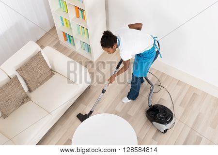High Angle View Of Young African Female Janitor Cleaning Hardwood Floor With Vacuum Cleaner poster