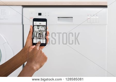 Close-up Of Woman's Hand Operating Dishwasher With Mobile Phone In Kitchen poster