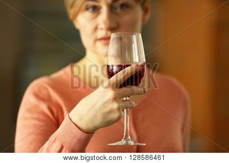 Beautiful middle-aged woman tasting red wine, close-up