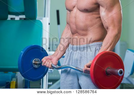 The man in the gym pumping abdominal muscles in a special simulator.