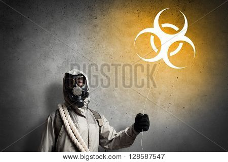 Man in respirator with radioactivity balloon in hands