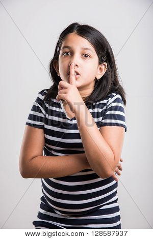 Beautiful indian little girl putting finger up to lips & ask silence onwhite background. asian girl child doing a Please Keep Quiet gesture towards the camera, indian small girl & silence please sign