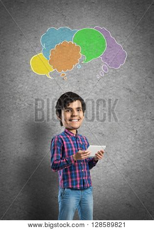 Funny bigheaded student with tablet in hands and colorful speech bubbles