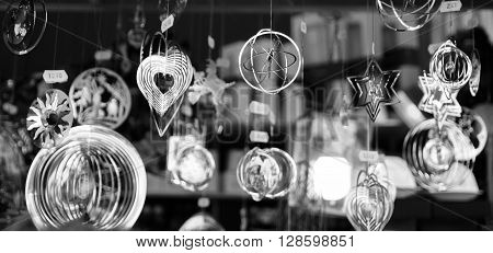 Shining silver decorations hanging on dark background.