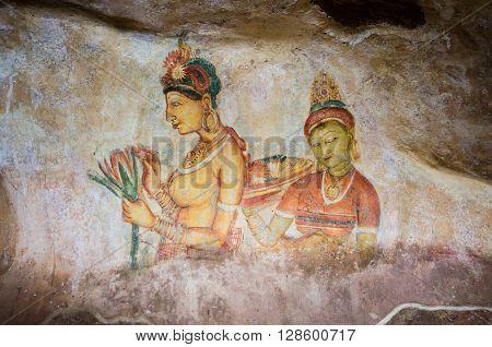 SIGIRIYA, SRI LANKA - MAY 30 2015: Photo of Apsara Frescoes on Mirror Wall at Sigiriya Rock Fortress, UNESCO World Heritage Site, Sri Lanka.