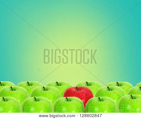 red apple place on retro green background among green apple with water droplet , unique or different concept