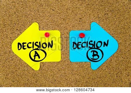 Message DECISION A versus DECISION B on yellow and blue paper notes as opposite arrows pinned on cork board with thumbtacks. Choice conceptual image poster