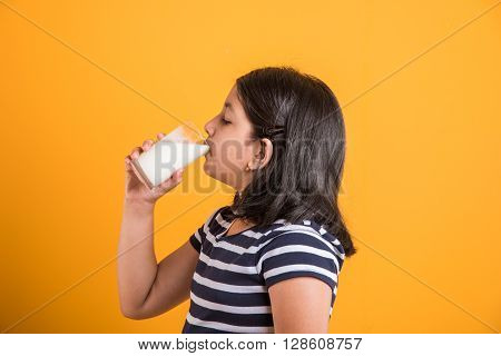 ndian girl with a glass of milk, asian girl drinking milk in a glass, portrait of small girl drinking milk in a glass over colorful background