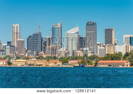 Sydney Australia - November 9 2014: Australian Sydney landmark - city CBD high rises and towers forming megapolis cityscape summer day from harbour Sydney New South Wales Australia. The Garden Island dockyard in the foreground.