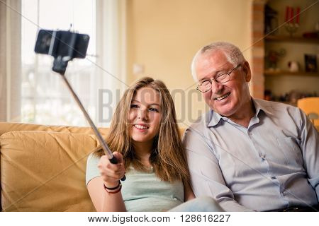 Teenage girl taking photo with mobile phone on selfie stick of herself and her grandfather at home
