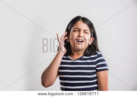 indian girl with ear pain, asian girl touching paining ear, stressful indian small girl with paining ear on white background