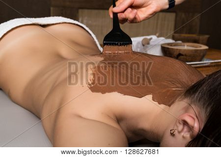 young girl in the spa salon, chocolate body wrap treatment, skin rejuvenation. Beauty treatment concept.