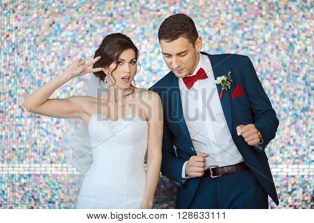 Wedding couple in love. Beautiful bride in white dress and veil with handsome groom in blue suite dancing and having fun indoors against beautiful colored background bokeh like their good mood. Close-up portrait of man and girl in fanny poses