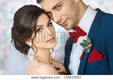 Wedding couple in love. Beautiful bride in white dress and veil with handsome groom in blue suite standing and embracing each other indoors against beautiful colored background bokeh like their dreams. Close-up portrait of man and girl looking at camera
