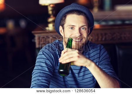 people, leisure, celebration and bachelor party concept - happy young man drinking beer at bar or pub
