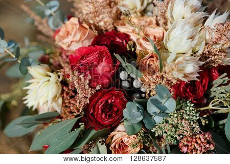 Beautiful wedding colorful bouquet for bride against nature background. Beauty of colored flowers. Bridal accessories. Female decoration for girl. Details for marriage and for married couple