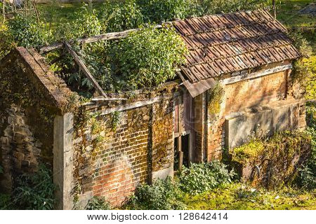 A very old house with the grass on its roof in Nepal.People might have left it during the maoist insurgency period a few years back.