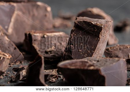 Chocolate. Black chocolate. A few cubes of black chocolate. Chocolate chunks. Chocolate bar pieces.