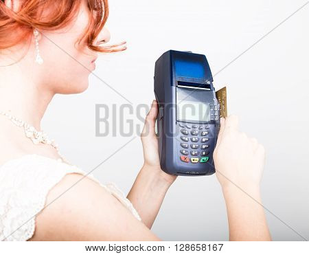 Payment card in a bank terminal. The concept of of electronic payment. Closeup of a beautiful bride holding credit card over payment terminal.